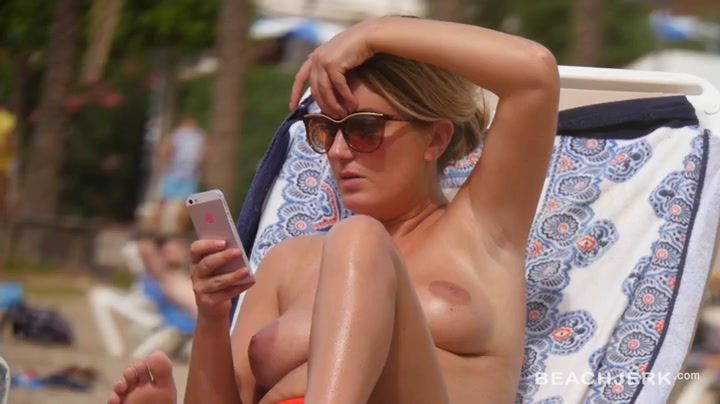 Topless chick lounging on the beach